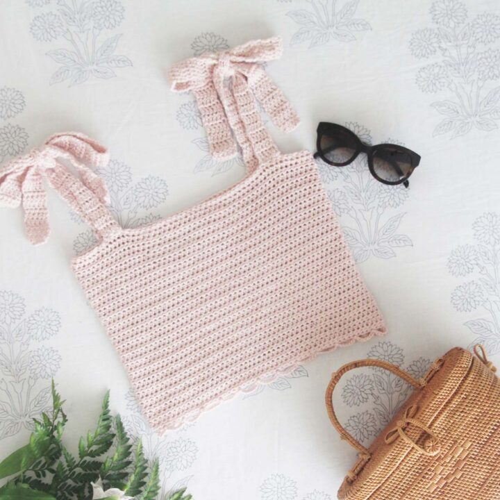 flat lay of baby pink crochet crop top with tie straps and scallop hem