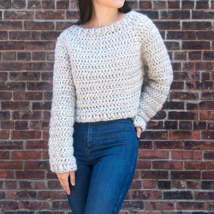 light grey chunky cropped crochet sweater with denim jeans