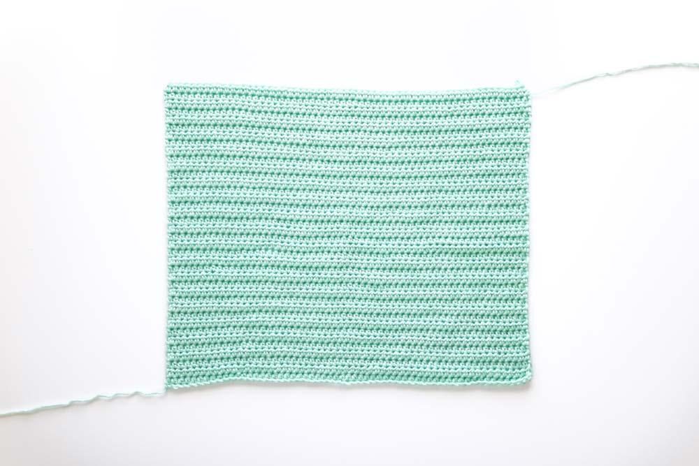back panel of cropped crochet sweater in mint green yarn