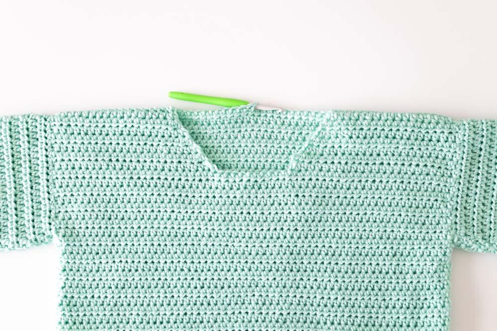 crochet hook inserted along neckline of crochet pullover