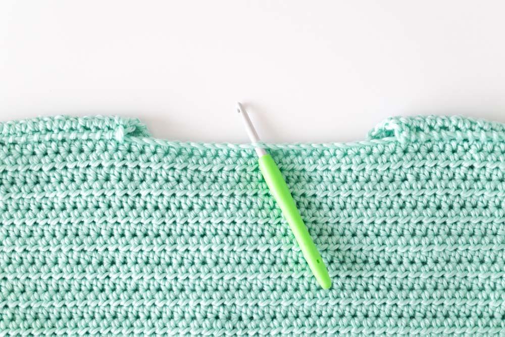crochet hook inserted in back of neck opening on crochet jumper