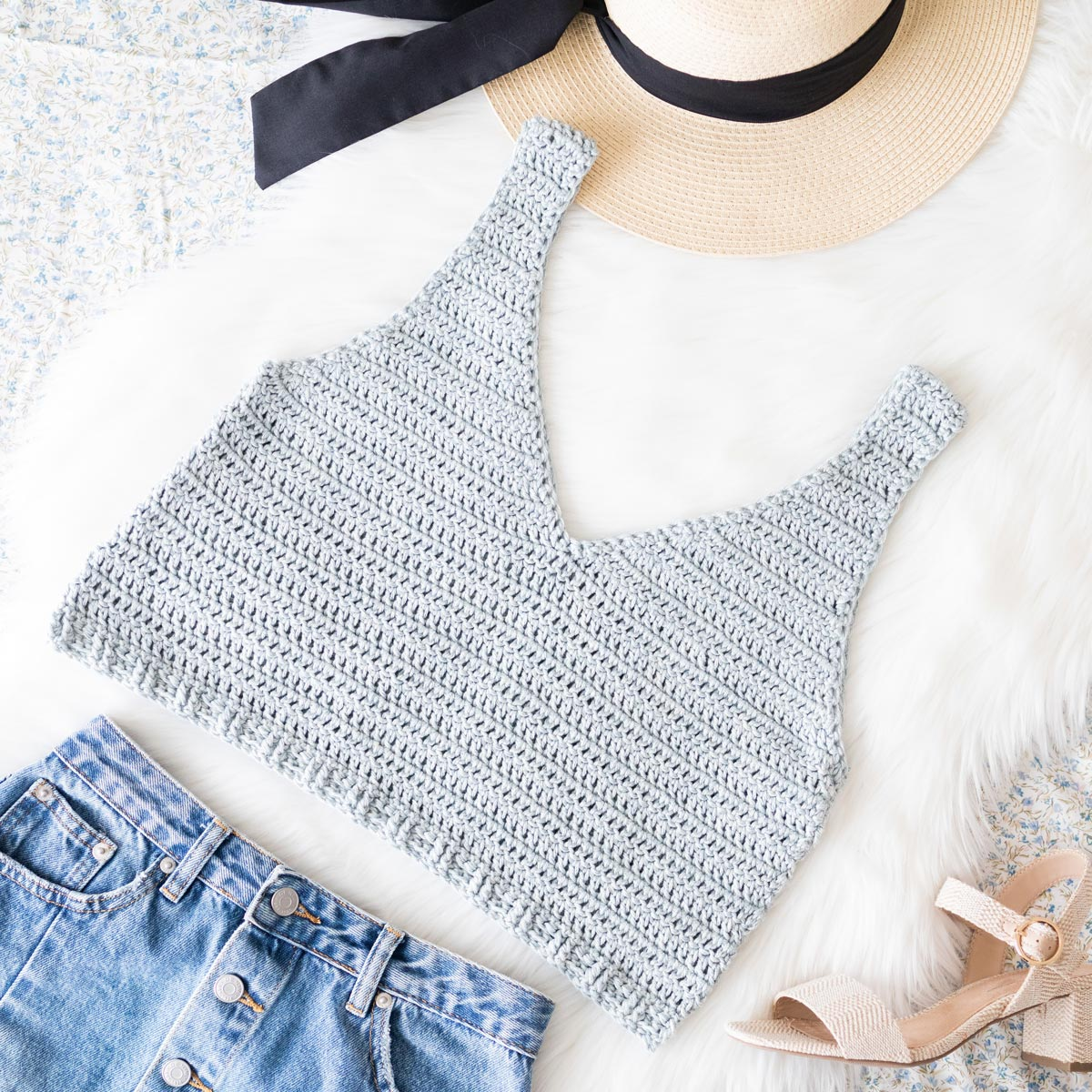 flat lay photo of easy v-neck crochet tank top in light blue denim yarn with jeans skirt and straw hat