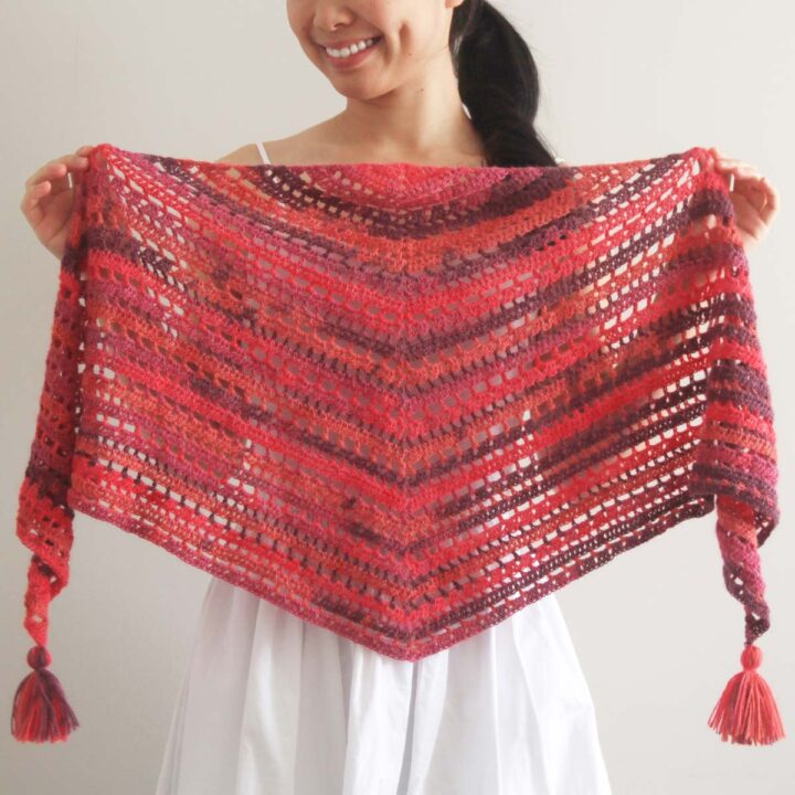 woman holding triangle crochet scarf with tassels
