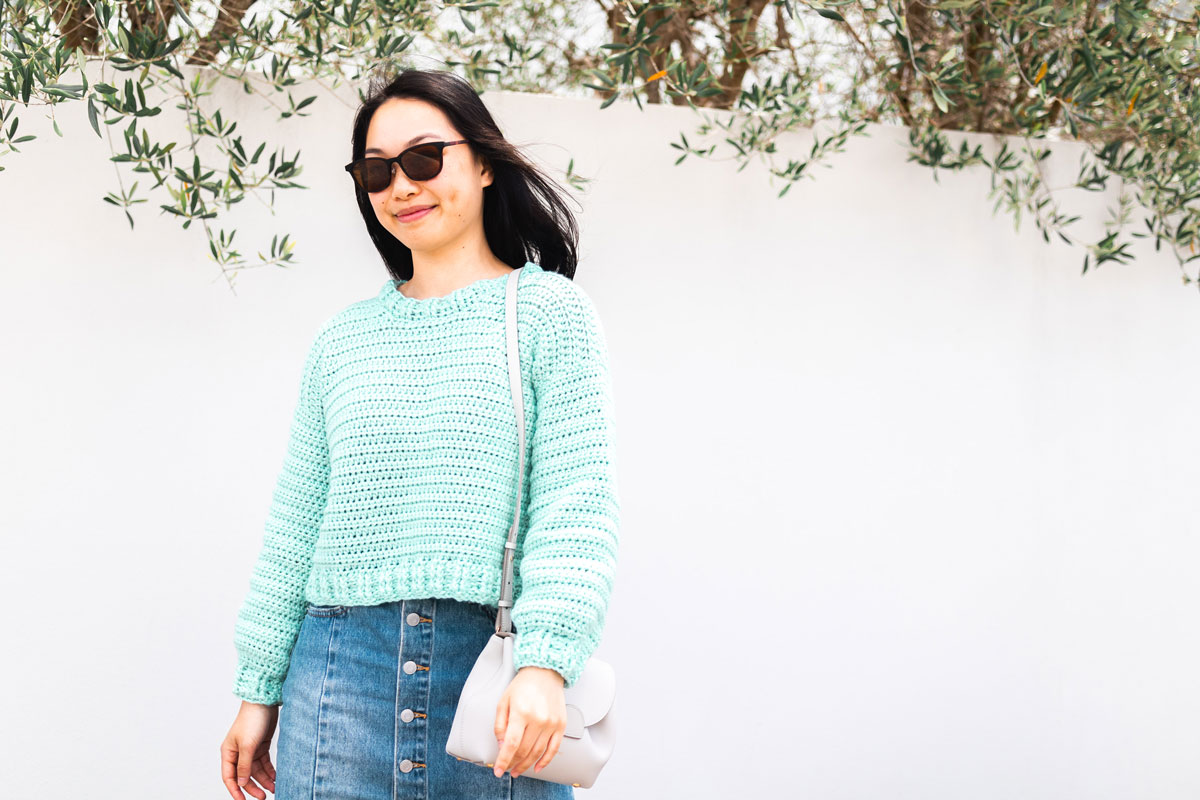 woman wearing green cropped crochet sweater and sunglasses