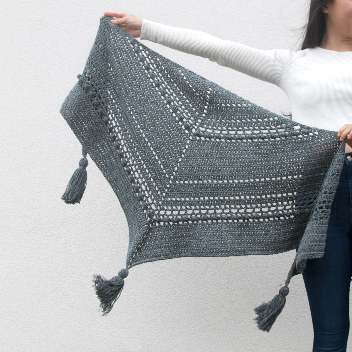 grey textured crochet wrap with bobble stitch, mesh stitch and chunky yarn tassels