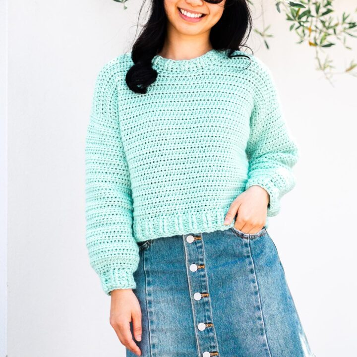 woman wearing handmade crochet cropped sweater in mint green yarn with denim mini skirt