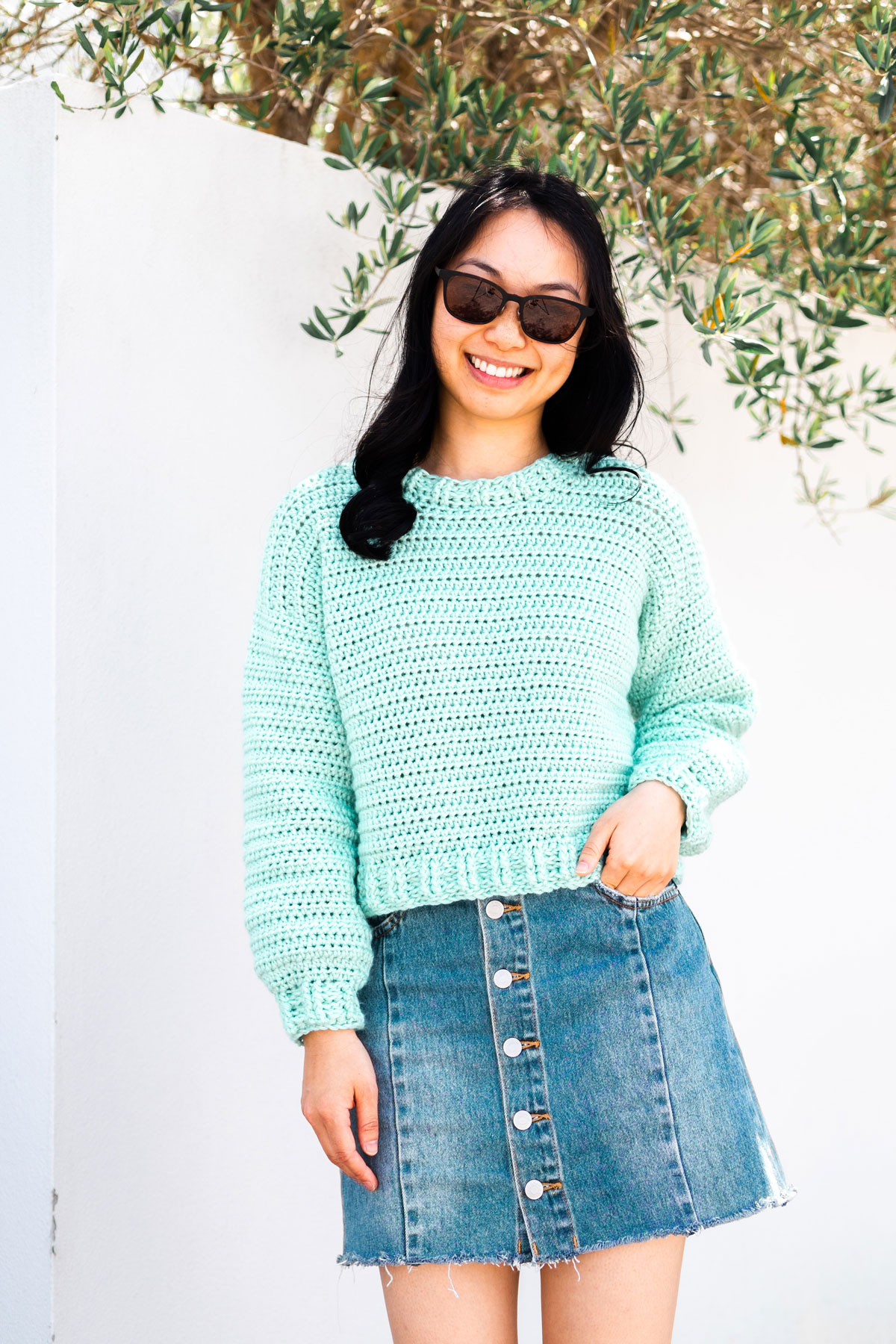 crochet designer wearing mint crop sweater pullover with denim skirt and sunglasses