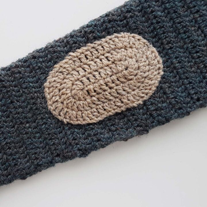 crocheted oval elbow patch sewn onto cardigan sleeve