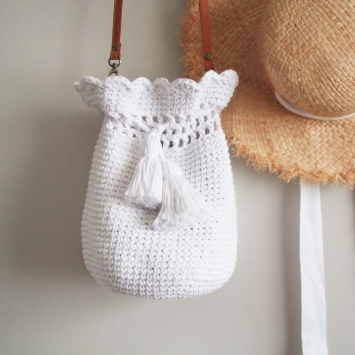 white crochet bucket bag with scallop stitch edging and tassel opening