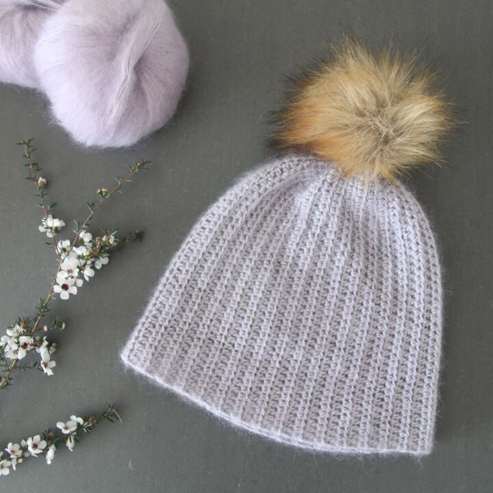 lilac fluffy mohair crochet beanie flat lay with skeins of silk mohair yarn