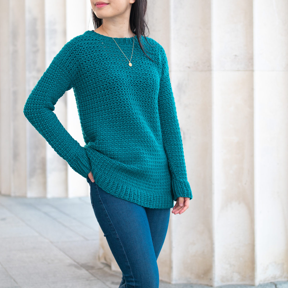 woman wearing emerald green long textured crochet sweater with blue denim jeans