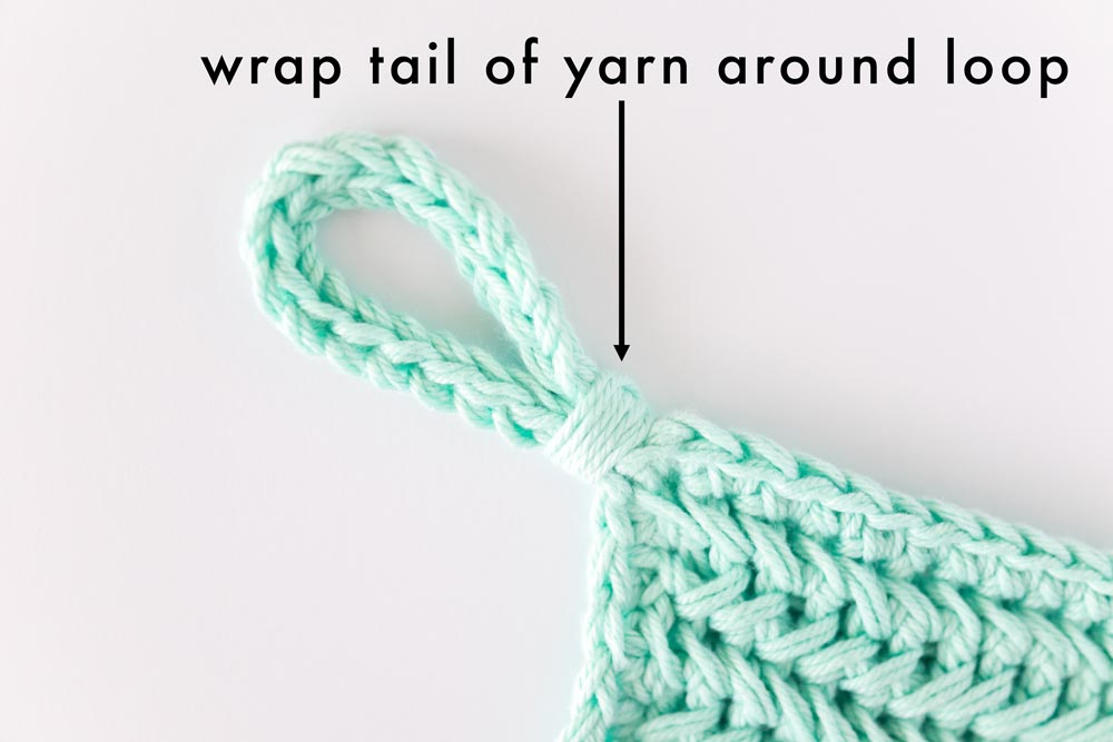 tail of yarn wrapped around base of chain loop