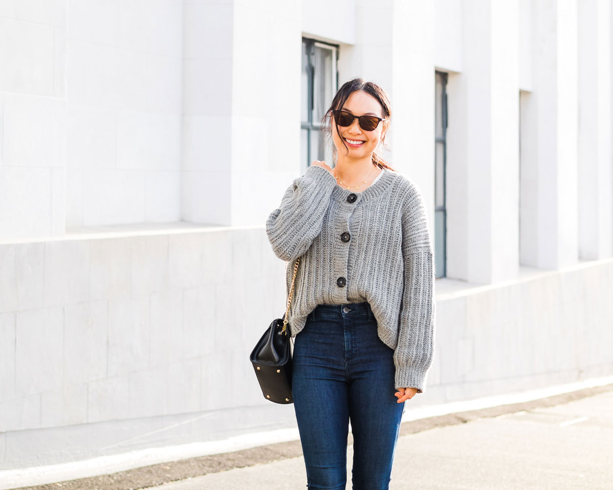 woman wearing ribbed grey crochet cardigan with large oversized sleeves, sunglasses and black handbag