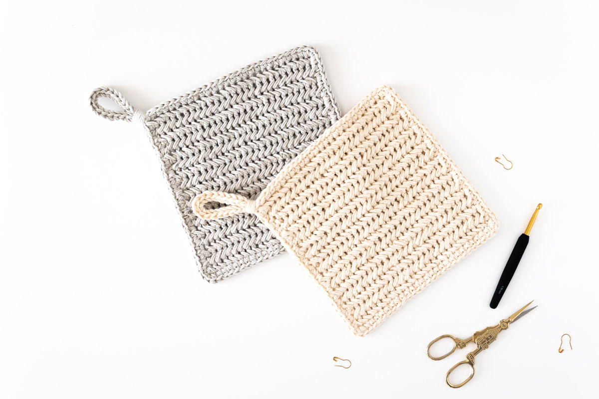 cream herringbone stitch pot holder on top of grey chevron hot pad with gold crochet hook, embroidery scissors and stitch markers