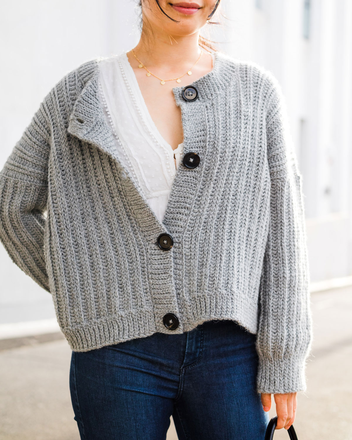 half unbuttoned grey alpaca yarn crochet cardigan with knit look ribbing and large black buttons