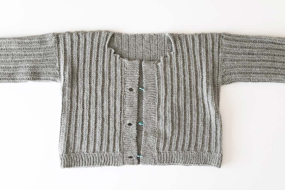 flat lay of ribbed crochet cardigan with buttonholes