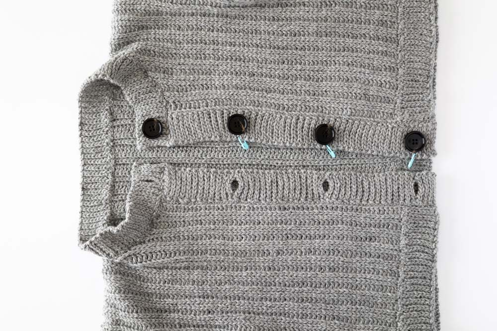 buttons placed on knit look ribbing with stitch markers to mark their place