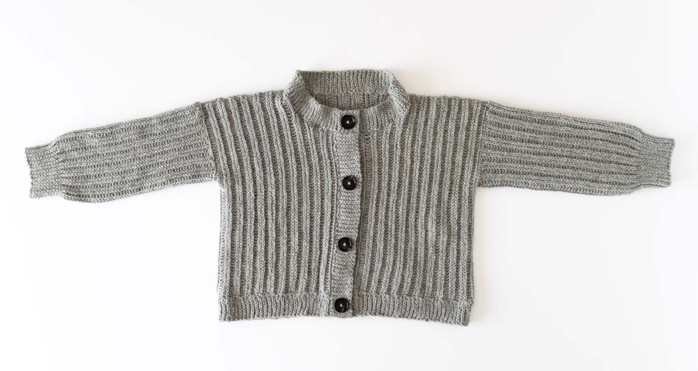 flat lay of ribbed crochet cardigan with buttons and a round neck