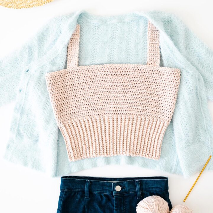 handmade modern crochet cropped tank top with ribbed hem on top of baby blue fuzzy cardigan
