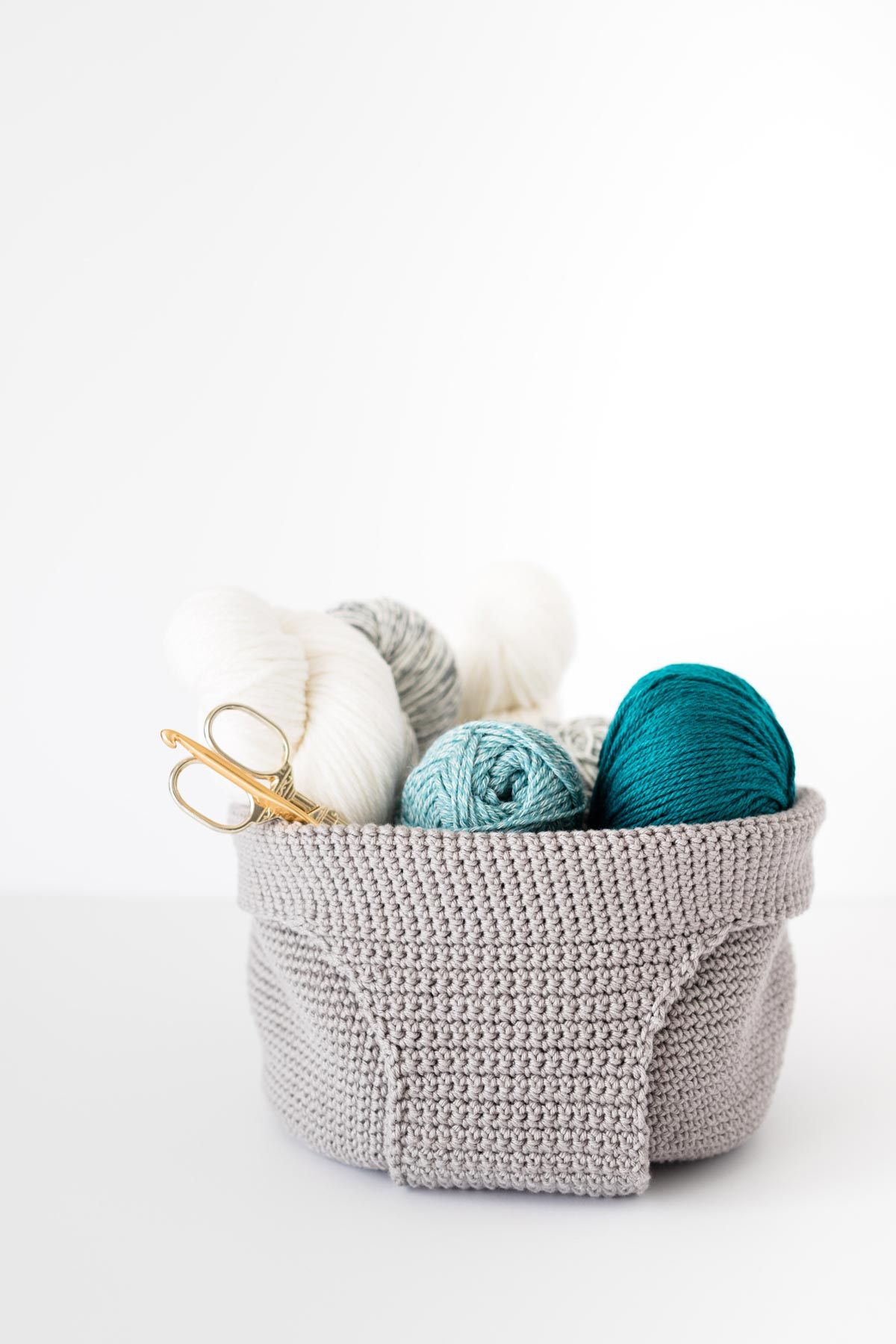 gray cotton crochet yarn basket full of yarn skeins and scissors and crochet hooks