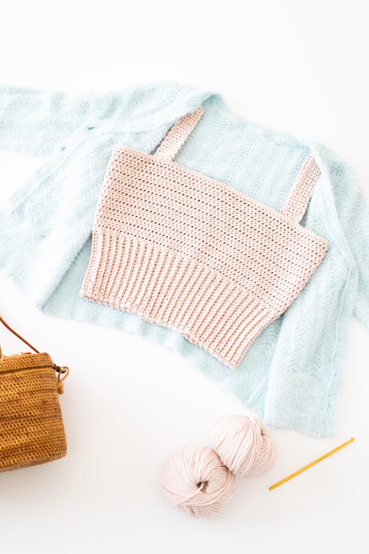 flat lay of summer crochet crop top with a ribbed hem on top of fluffy light blue cardigan with gold 5mm crochet and 2 skeins of yarn
