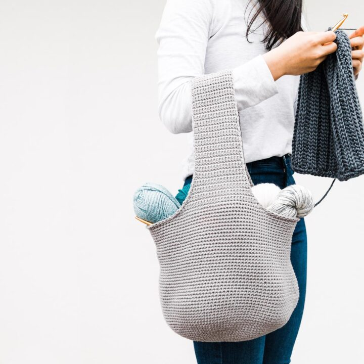 woman crocheting a beanie while carrying crochet project yarn bag tote