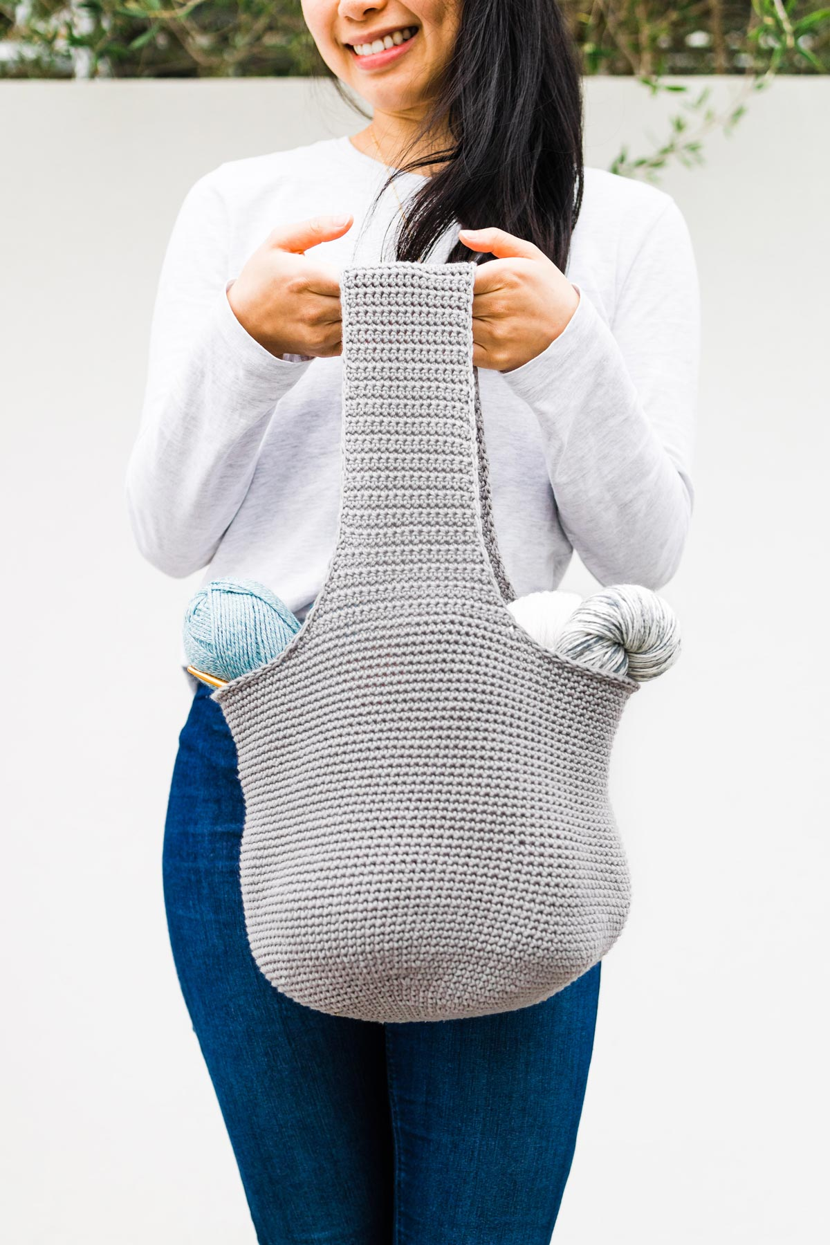 woman holding large crochet tote bag full of yarn skeins