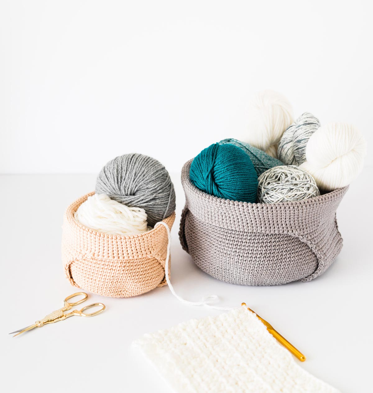 two crochet project bags with handles folded over to form yarn baskets fill of yarn