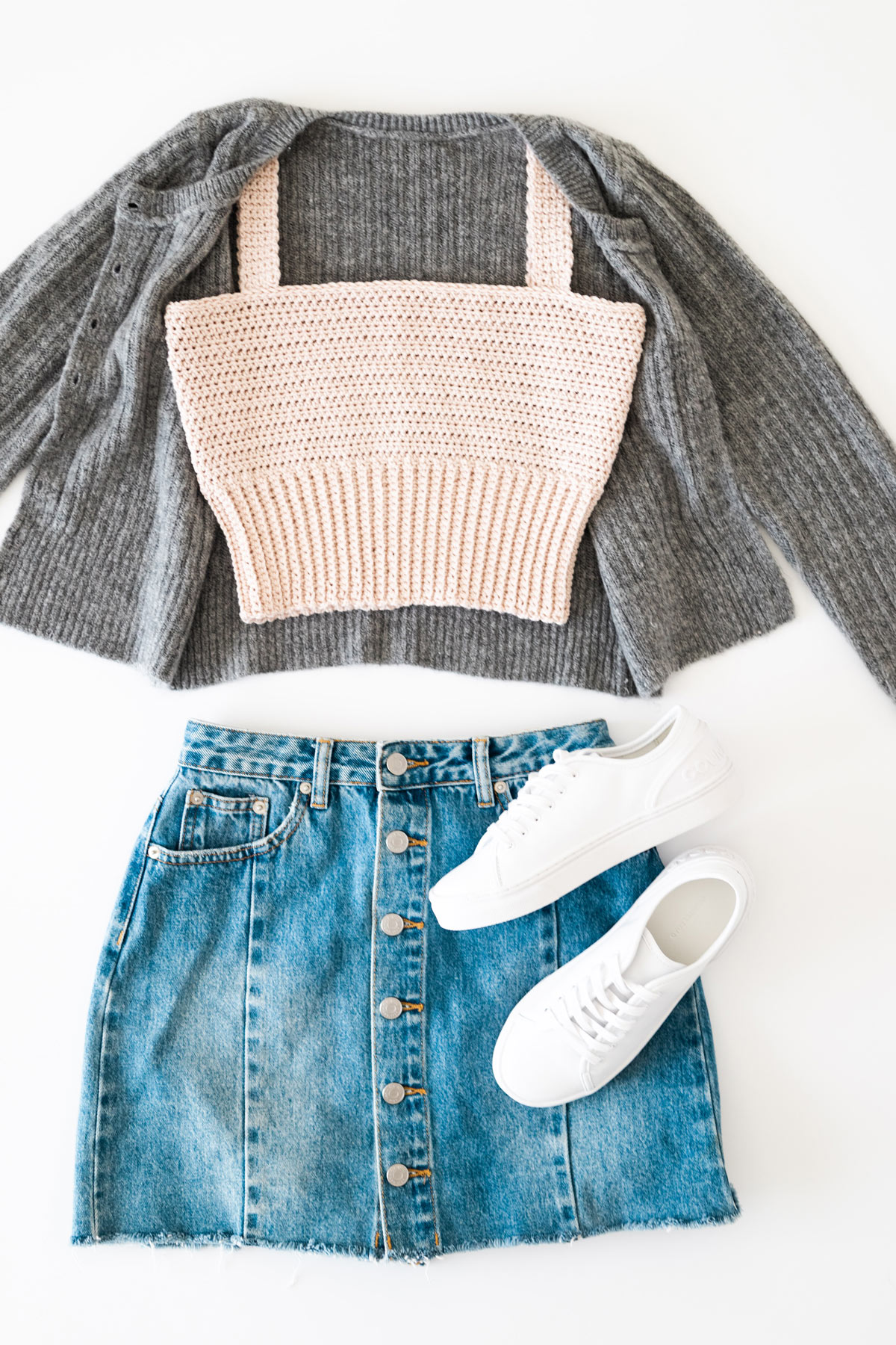 flat lay of cotton tank top with grey cardigan and denim mini skirt and white sneakers