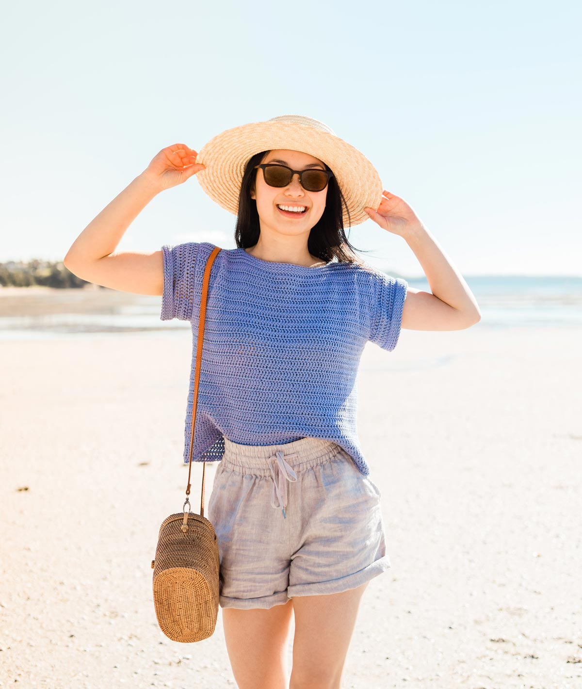 woman wearing a boxy crochet crop top with linen shorts, sunglasses and rattan bag