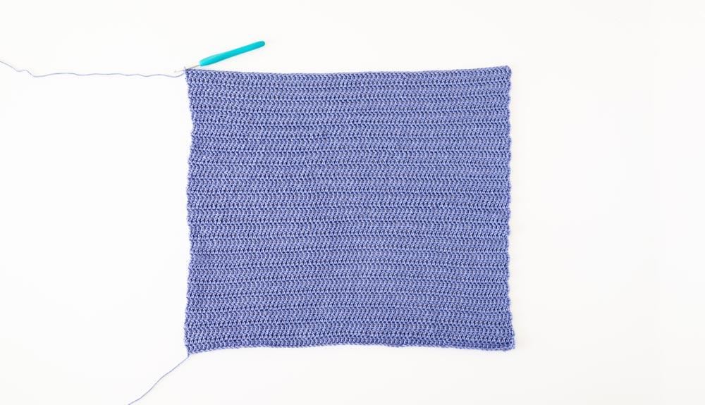 flat lay of crochet summer top back panel in purple cotton yarn