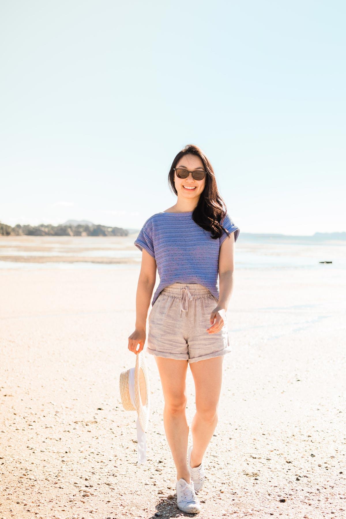 woman walking on beach wearing lilac cotton crochet t-shirt holding straw hat