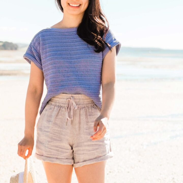 woman wearing handmade crochet shirt with linen shorts and straw hat