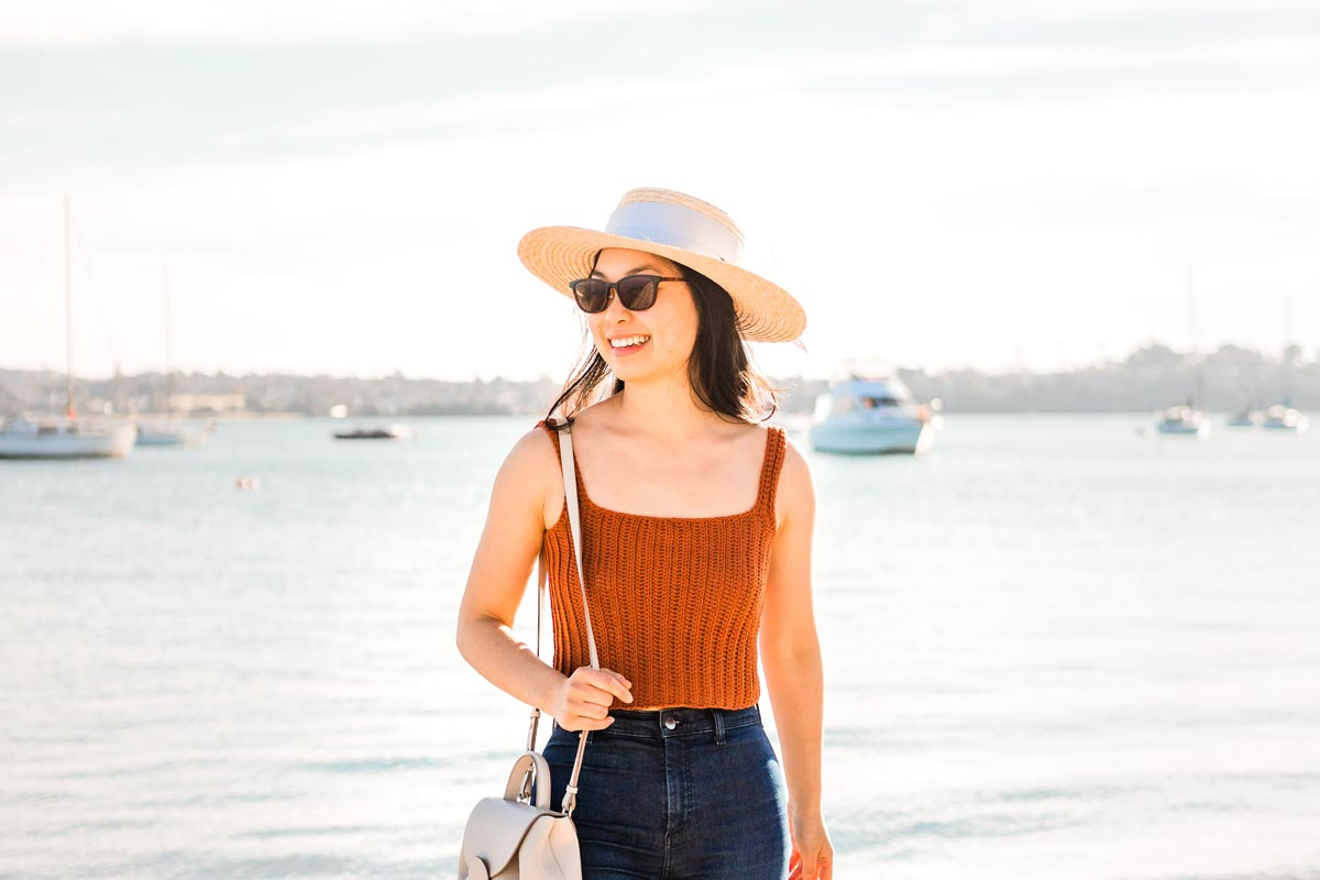 woman wearing handmade crochet ribbed crop top with square neck, high waisted jeans, straw hat, sunglasses and white bag