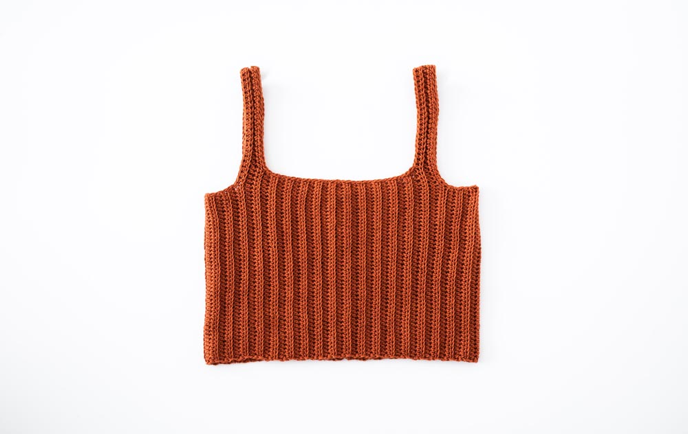 flat lay of finished ribbed crochet crop top camisole singlet tank