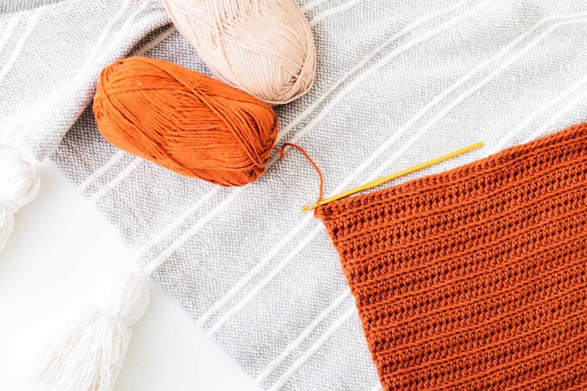 flat lay of half double crochet swatch in wecrochet knit picks cotlin cotton linen yarn with gold crochet hook