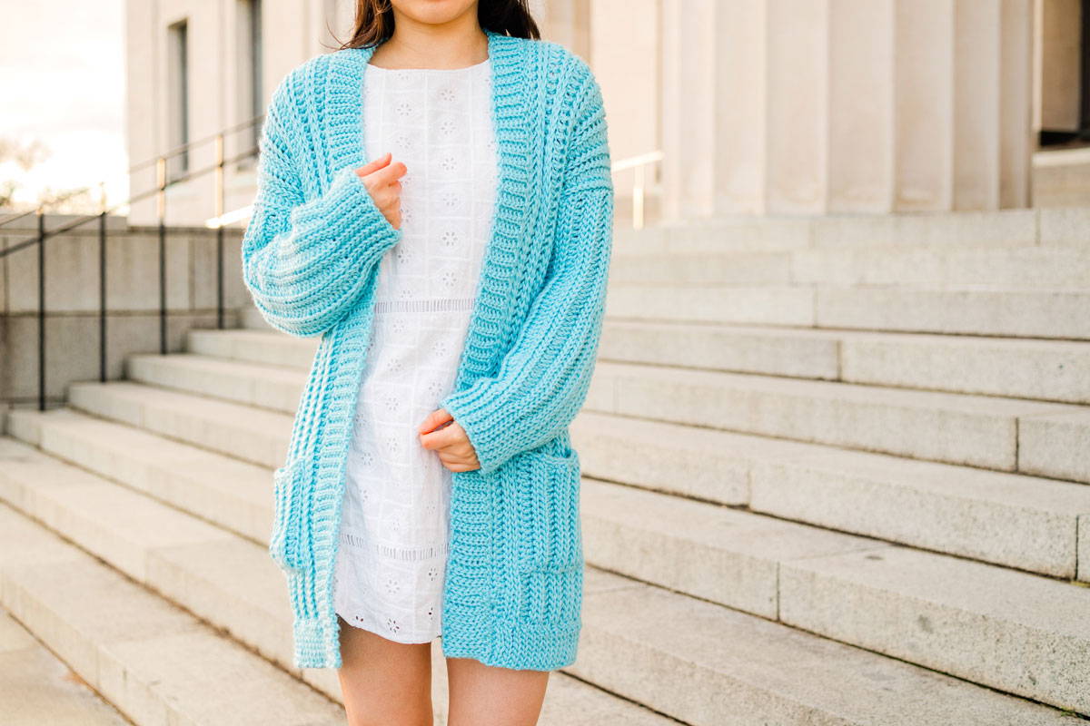 woman wearing slouchy ribbed crochet cardigan while holding neckline ribbing