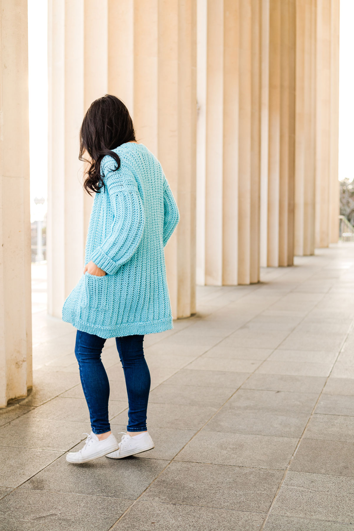 side view of model wearing ribbed crochet cardigan with slouchy sleeves and pockets