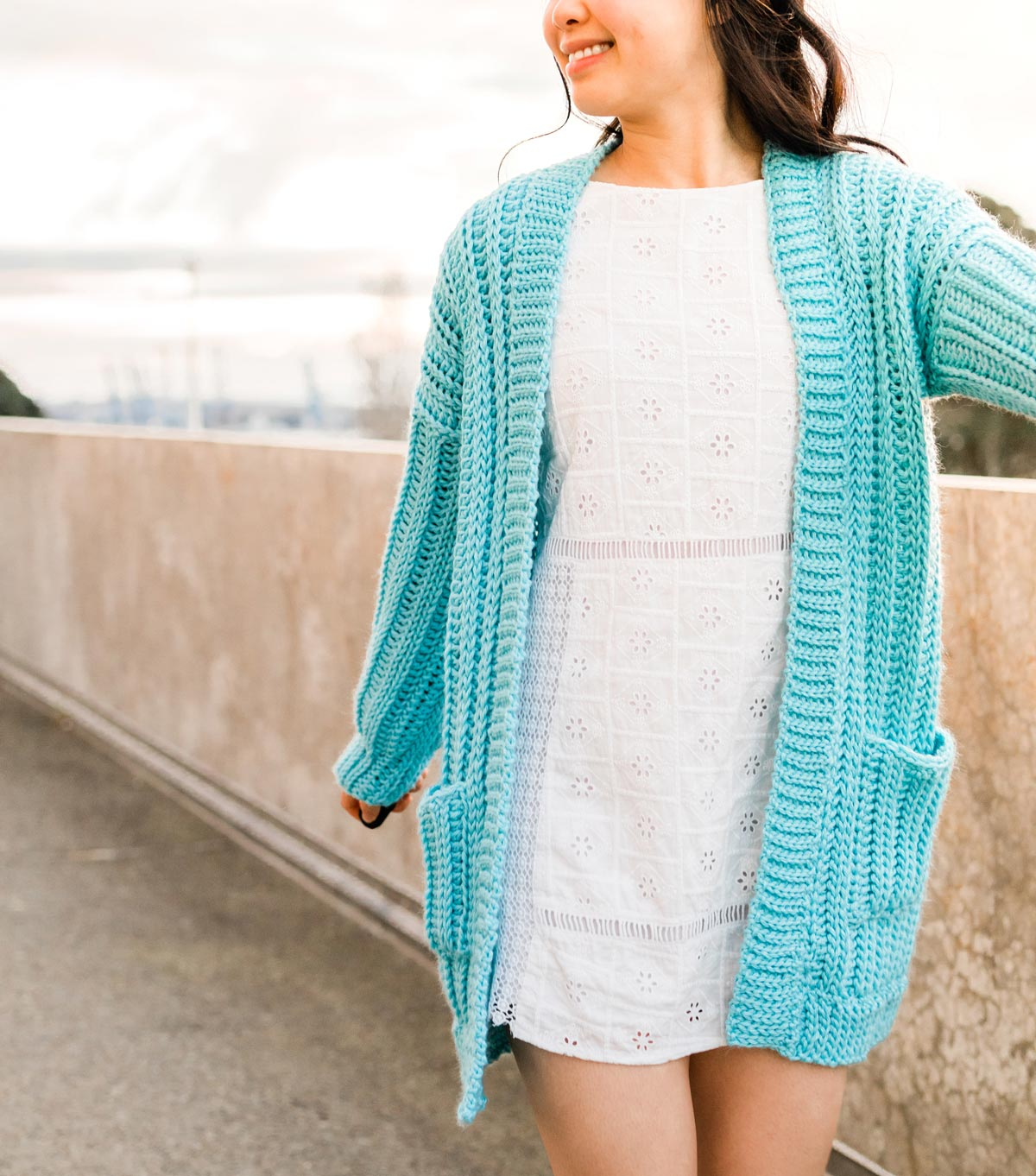 woman wearing blue ribbed slouchy crochet cardigan with pockets