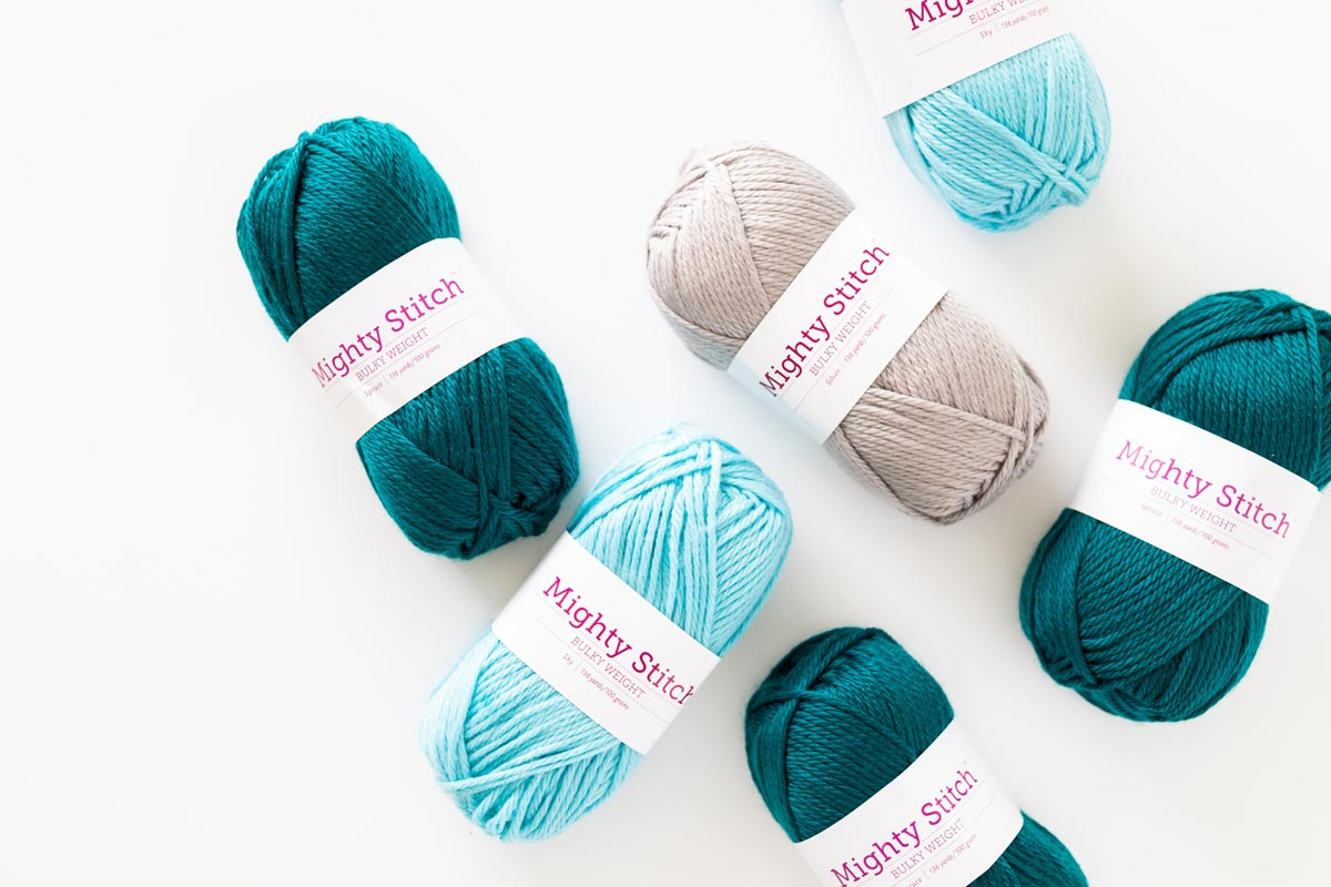 flat lay of we crochet knit picks mighty stitch bulky yarn in blue green and grey