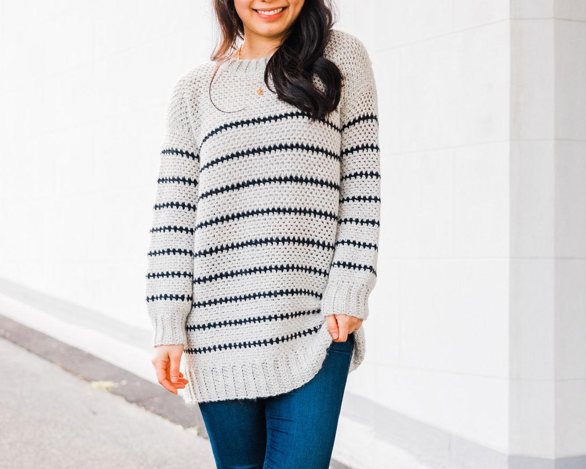 woman wearing long crochet stripe sweater in grey and navy