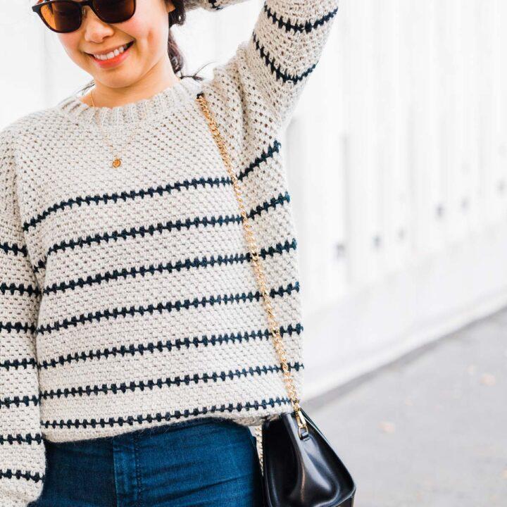 woman wearing linen stitch crochet sweater in grey yarn with navy blue stripes