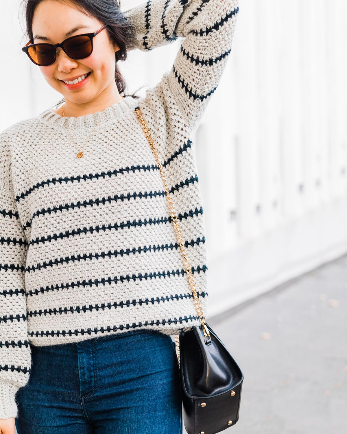 close up on model wearing linen stitch crochet sweater with half double crochet ribbing