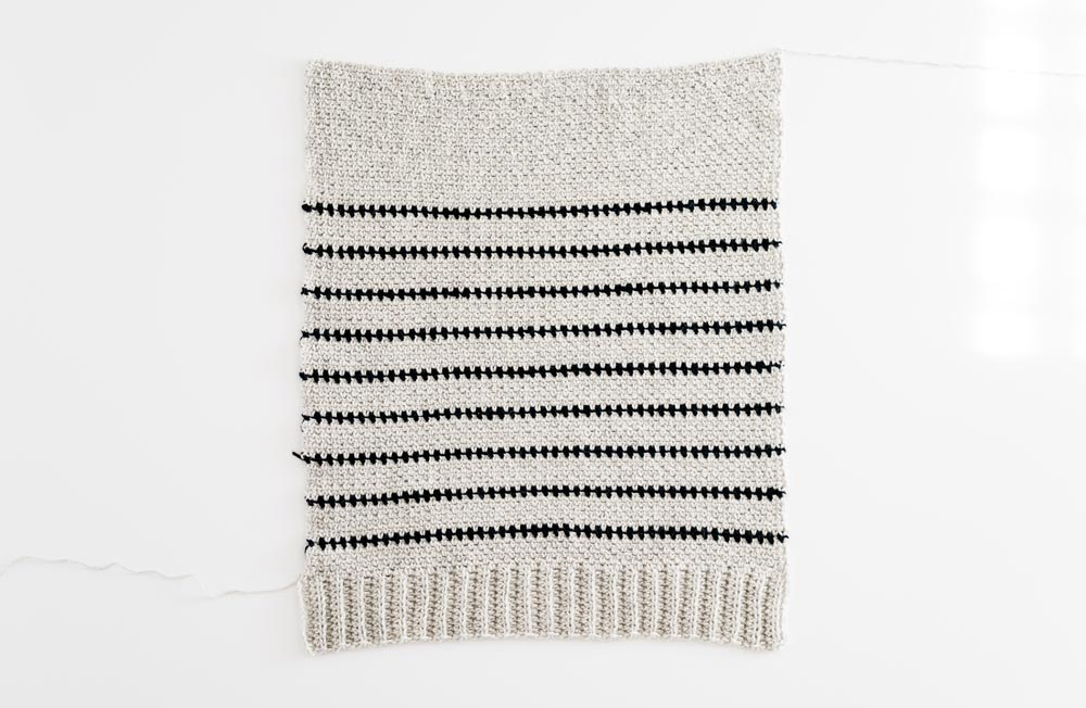flat lay of striped crochet sweater back panel