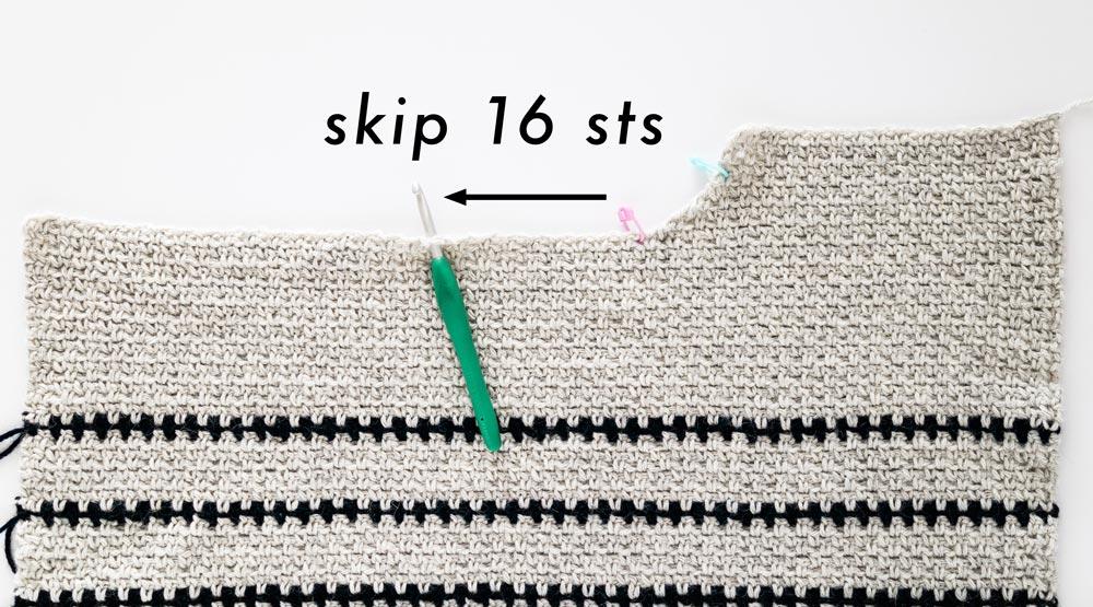 crochet hook inserted along neckline of front panel of crochet sweater