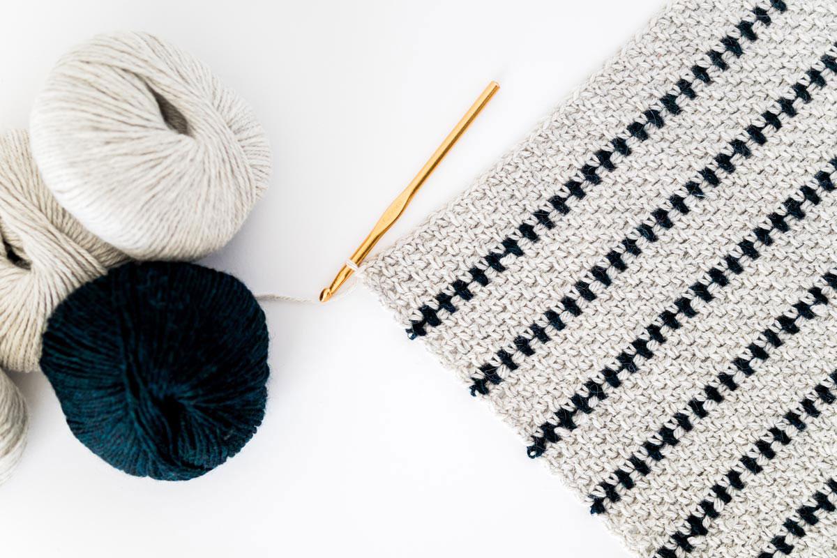 flat lay of crochet moss stitch swatch in grey and navy abby alpaca yarn